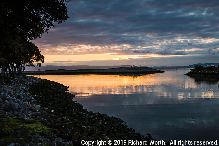 A soft golden sunset reflects along the rocky shoreline at the San Leandro Marina along eastern shores of San Francisco Bay.
