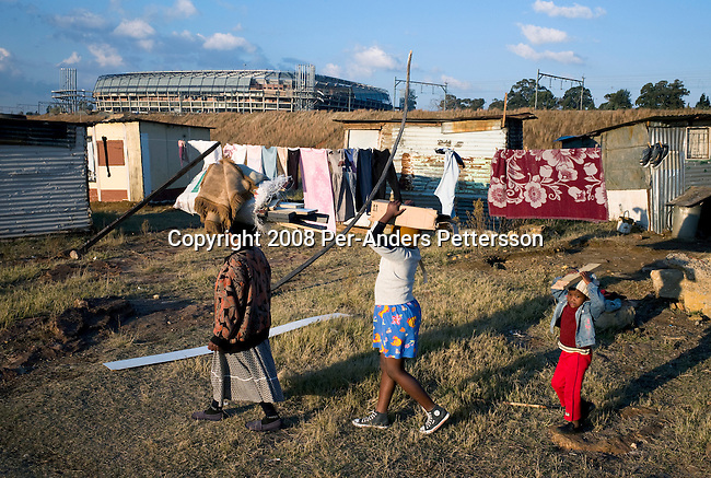 SOWETO, SOUTH AFRICA - JUNE 21:  A family carries firewood in a poor shantytown in front of the newly constructed Orlando Stadium on June 21, 2008 in Soweto, South Africa. Many people still live in poverty in townships around South Africa, without proper housing, sanitation and electricity. The stadium will be used as a training ground for he upcoming Soccer World Cup in June 2010 and also used for games in the local soccer league. (Photo by: Per-Anders Pettersson/Getty Images)..