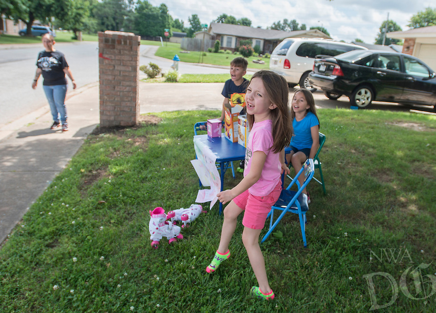 NWA Democrat-Gazette/ANTHONY REYES &bull; @NWATONYR<br /> Raiden Dale, 7, (from left), Kaylen Dale, 7, and Emily Dale, 9, call out to passerbys Monday June 13, 2016 as their aunt Crystal Dale looks on as they sell treats outside their home in Springdale. The trio were selling granola bars, gummy fruit snacks and puppets to passing motorists on their neighborhood street. Raiden hope to buy trading cards with his share of the money.