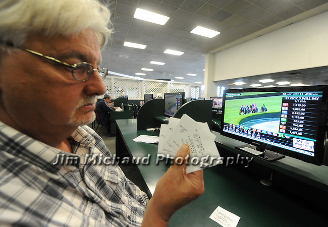(Boston Ma 060615)  Nick Palumbo, 64, of Lowell, looks over his tickets for the race, including American Pharoah, during the Belmont Stakes, Saturday, June 6, 2015, at Suffolk Downs in Boston. Herald Photo by Jim Michaud