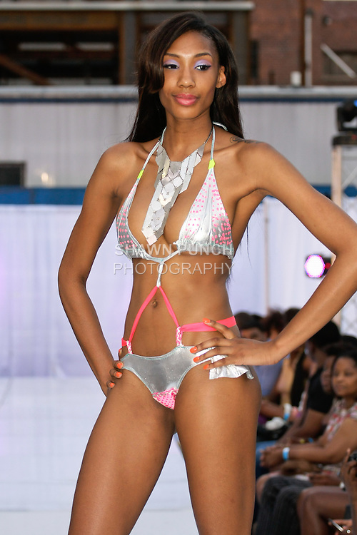 Model walks runway in a Naked Roots Collection swimsuit by Eunika Simmons,  during the JRG