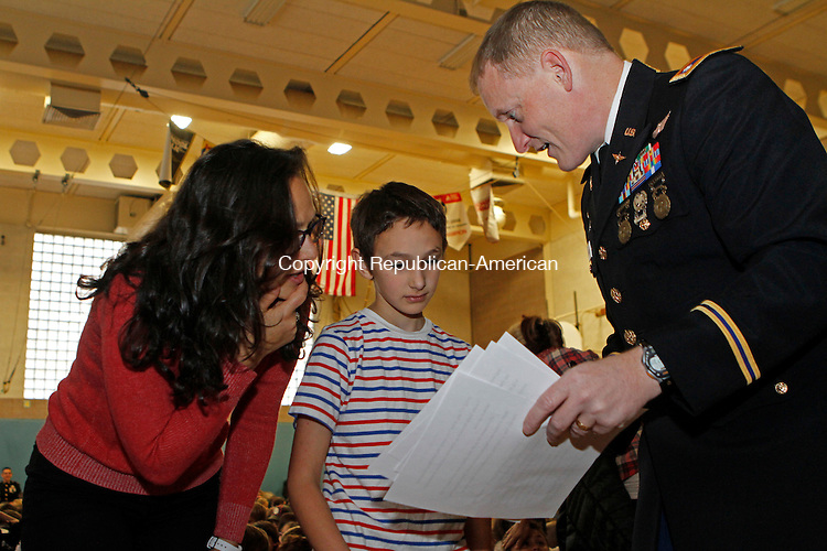 Southbury, CT-111116MK01 lieutenant Col. Army National Guard Jeffrey Lapierce reviews notes for his keynote speech with fourth grader Michael Schimenti as his mom Stefanie looks on just before the Veterans Day ceremony held at Pomperaug Elementary School on Friday Michael Kabelka / Republican-American.
