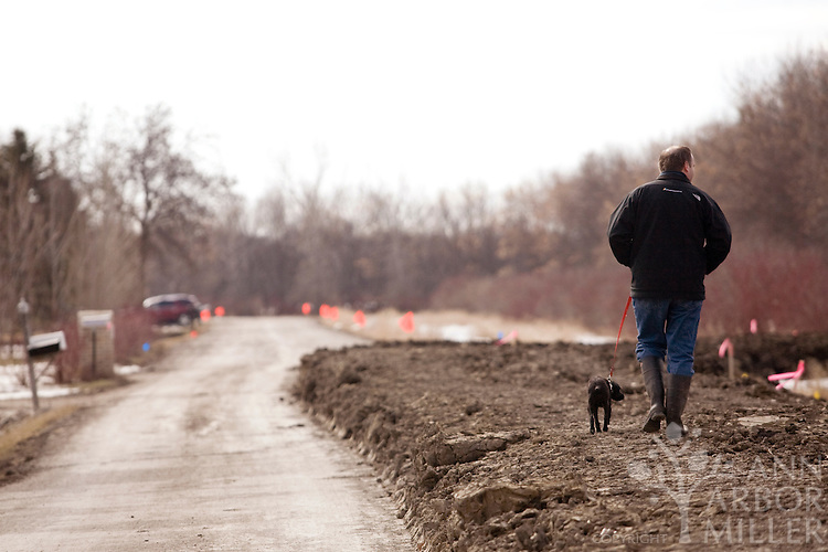 With a clay dike occupying half of a street in the Forest River development south of Fargo,N.D., area resident Steve Harter and puppy Buster had limited places to walk on Saturday morning (March 20, 2010). Residents in rural North Dakota and Minnesota are dealing with overland flooding, swollen rivers and elaborate dike systems.