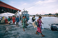 Marshallese islanders disembark the U.S. Army ferry that connects Ebeye Island with Kwajalein Island where they work at the U.S. military base.