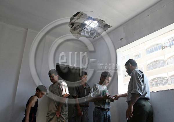 GAZA CITY - GAZA - 24 JULY 2007 -- Palestinian's examining the punctured roof inside the building. An Israeli air strike injured at least five Palestinians in Gaza City, said witnesses and doctors. -- PHOTO: EUP-IMAGES / Thair ALHASSANY
