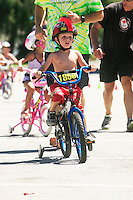 A young boy races his training wheeled bicycle in the Splash n Dash as dad runs along behind him. The annual Splash n Dash is an opportunity for young kids to compete for the first time against other children.