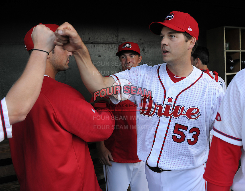 Left handed pitcher Rich Hill (53) of the Boston Red Sox is congratulated in the dugout after throwing a perfect inning in a Major League rehab assignment with the Greenville Drive in a game against the Lakewood BlueClaws on April 7, 2012, at Fluor Field at the West End in Greenville, South Carolina. (Tom Priddy/Four Seam Images).