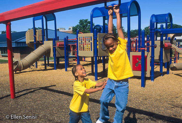 MR / Schenectady, NY.Zoller Elementary School.Twin girls (age 7; African-American and Caucasian) slide on sliding bar in school playground..MR: Puc1 Puc2.© Ellen B. Senisi.MR: Cal1 Cal3.© Ellen B. Senisi