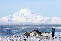 A photographer takes a picture of Mount Redoubt volcano from the Cook Inlet beach in Kenai, Alaska, as it vents steam during a period of volcanic unrest. The mountain is prominent on the horizon in Kenai, about 50 miles across Cook Inlet to the west.