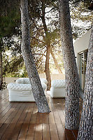 Retaining three mature pine trees and building the deck around them provides shade from the punishing summer sun, but also anchors the house in the natural environment.