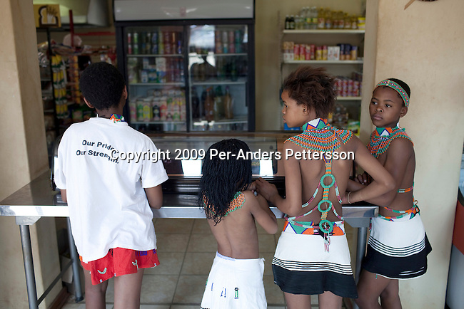 LUDZIDZINI, SWAZILAND - AUGUST 31: Unidentified children buy snacks at a shop at the Royal Palace on August 31, 2009, in Ludzidzini, Swaziland. About 80.000 virgins from all over the country attended this yearly event, which goes on for a week and which is the biggest in Swazi culture. Many of the girls stayed in tents and slept on the ground. It was founded to celebrate the beauty of Swazi women and girls. King Mswati III, and absolute monarch, was born in 1968 and he has 14 wives and many children. The king danced with his men in front of the 80.000 girls. Many of the girls hope to get noticed by the king and to be chosen as a future wife, a ticket from poverty and into a life of privilege and luxury. The country is one of the poorest in the world and it is struggling with a high prevalence of HIV-Aids and severe poverty. (Photo by: Per-Anders Pettersson)...