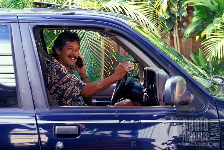 Honolulu businessman talking on cellular phone in car