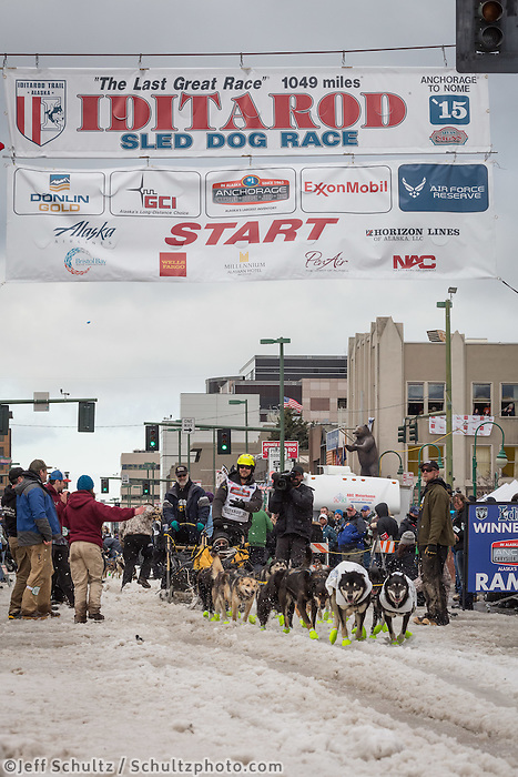Brent Sass and team leave the ceremonial start line with an Iditarider at 4th Avenue and D street in downtown Anchorage, Alaska during the 2015 Iditarod race. Photo by Jim Kohl/IditarodPhotos.com
