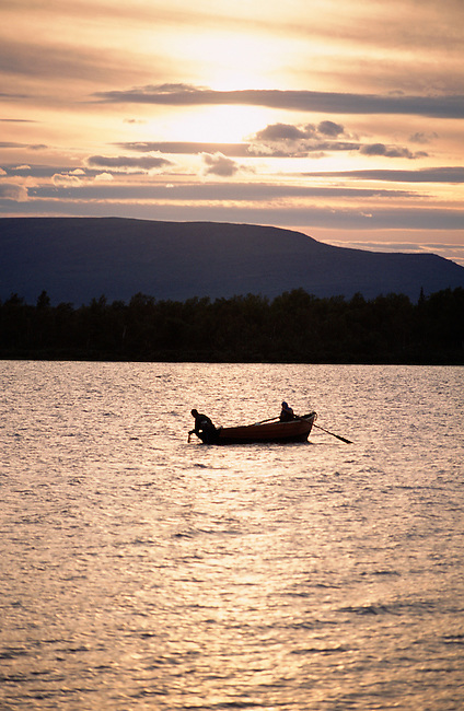 Two Sami men out checking their fishing nets in a wooden boat at sunset near Lovozero (Strong Lake). Kola Peninsula, NW Russia.