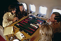 Hugh Hefner plays backgammon aboard his lear jet. 1973. Photo by John G. Zimmerman.