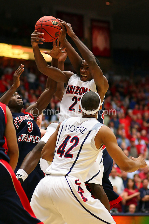 Nov 17, 2008; Tucson, AZ, USA; Arizona Wildcats guard Kyle Fogg (21) grabs a rebound over forward Jamelle Horne (42) and Florida Atlantic Owls forward Chris Watson (3) in the first half of a NIT Season Tip-Off game at the McKale Center.  Arizona won the game 75-62.  Mandatory Credit: Chris Morrison-US PRESSWIRE