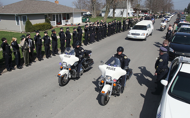 Hundreds of law enforcement officers line the street to salute the hearse carrying Sgt. Eric Stein as it passes Saturday, April 9 in Sigourney.  Stein was shot and killed in the line of duty.