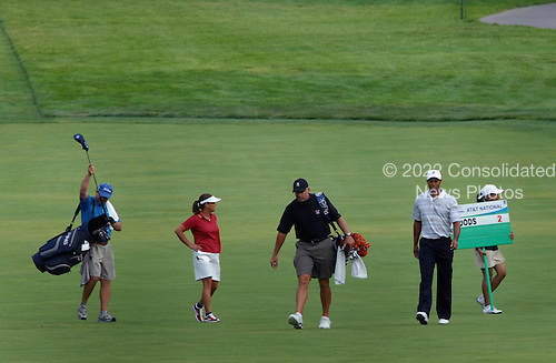 Bethesda, MD - July 4, 2007 -- Army Sergeant Major Mia Kelly, in red shirt, and Tiger Woods in white, walk the fairway with their caddies during the inaugural Earl Woods Memorial Pro-Am.  Along with Kelly, Woods teed off in the early morning with AT&T Chairman Randall Stephenson and Air Force Sergeant Andrew Amor for a round of 18 holes at Congressional Country Club in Bethesda, Maryland on Wednesday, July 4, 2007.  Woods and company was later joined near the 16th hole by former United States President George H.W. Bush and his wife Barbara.  The commemorative occasion pays tribute to the many courageous men and women serving in our armed forces during the week of our nation's independence celebration. .Credit:  Johnny Bivera - DoD via CNP.