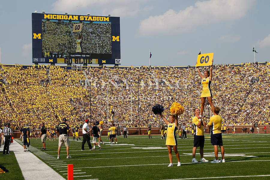 Michigan cheerleaders pump up the 110,000-plus crowd during the season opener against Western Michigan, Saturday, Sept. 3, 2011 in Ann Arbor, Mich. (Tony Ding for The New York Times)