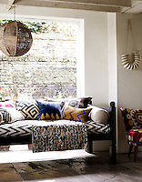Interior in location house, London. Geometric patterned sofa, laden with cushions, sits in front of a large, bright window. A large, woven light shade hangs above. Styling by Alison Nicholls.