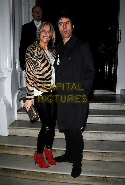 NICOLE APPLETON & LIAM GALLAGHER .Attending the Pretty Green clothing label launch party, the Gore Hotel, Queen's Gate, London, England, UK,.7th November 2009..full length black coat white motif print t-shirt trousers couple married husband wife tiger zebra animal print jacket shiny wet-look leggings pvc red ankle boots mac trench slogan belt clutch bag steps buckles zebra gold .CAP/CAS.©Bob Cass/Capital Pictures