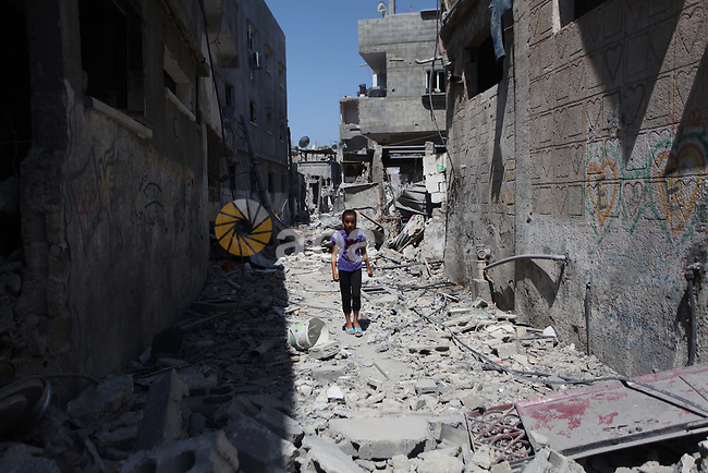 A Palestinian girl walks on rubble of her house during a 72-hour ceasefire observed in the Gaza Strip on August 11, 2014 in the northern Beit Hanun district of the Gaza Strip. Almost 12 hours into the truce, the skies over Gaza remained calm, with no reports of violations on any side and signs of life emerging on the streets of the war-torn coastal enclave which is home to 1.8 million Palestinians. Photo by Ashraf Amra