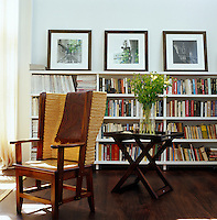 A wicker-backed armchair in a corner of the living room which has walls lined with bookshelves