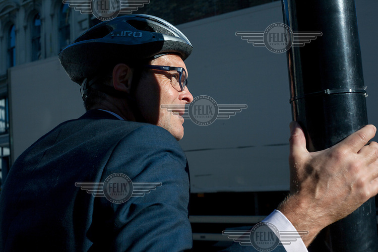 A cyclist waits at a traffic light.