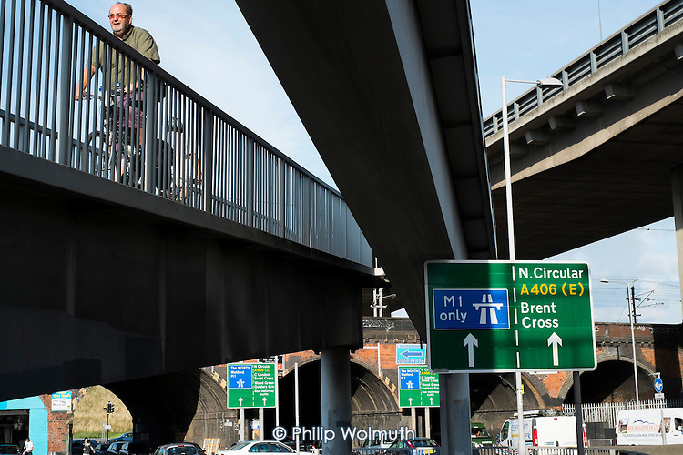 A cyclist on a raised walkway next to the North Circular Road flyover and the slip road to the M1 motorway at Staples Corner, London.