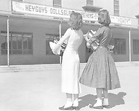 Two coeds looking at poster advertising the San Souci Club at Arlington State College, 1958