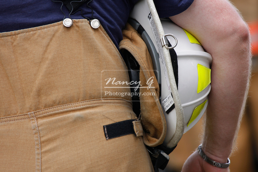 A firefighter holding his white helmet under his arm