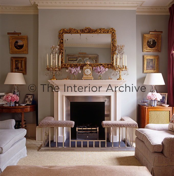 The pale blue drawing room is traditionally furnished with a club fender around the fireplace