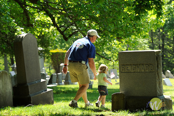 Wildwood Cemetery. Memorial Day services..Child at gravestones with Grand-dad.