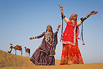 Rajasthani dancers in traditional costumes performing on sand dunes in the Thar Desert;.Camel driver with camels in background: Rajasthan, India --- Model Released