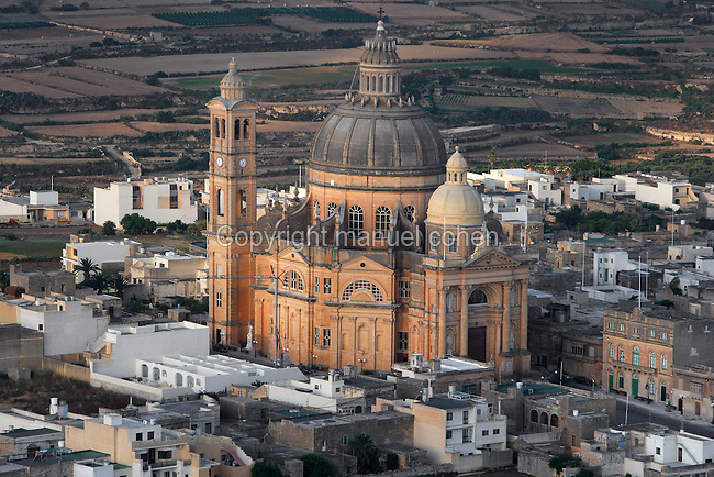 Aerial view of the Church of St John, 20th century, Xewkija, Gozo, Malta, pictured on June 7, 2008, in the morning. The Republic of Malta consists of seven islands in the Mediterranean Sea of which Malta, Gozo and Comino have been inhabited since c.5,200 BC. It has been ruled by Phoenicians (Malat is Punic for safe haven), Greeks, Romans, Fatimids, Sicilians, Knights of St John, French and the British, from whom it became independent in 1964. Xewkija became a parish in 1678 and its original church was consecrated in 1755. The new church, 1951-78, designed by Joseph D'Amato, and inspired by the Basilica of Santa Maria Della Salute, Venice, features a huge rotunda and dome 75 metres high and 28 metres in diameter. The old church has been rebuilt next door. Picture by Manuel Cohen.