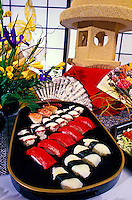 A beautiful oval Japanese black lacquer tray loaded with an assortment of sushi, set on a table with floral fans and a vase of yellow and purple flowers with shoji screens in the background.