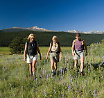 Girlfriends hiking in meadow of wildflowers on a clear, blue-sky summer morning at Moraine Park in Rocky Mountain National Park, Colorado (MR#85)