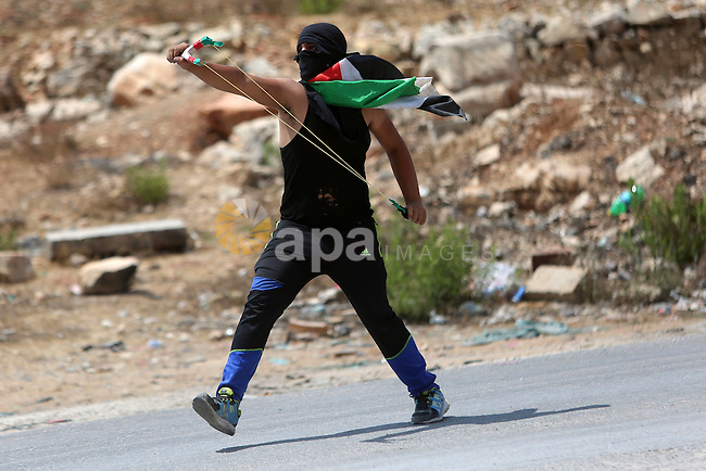 A Palestinian protester uses a slingshot to hurl stones towards Israeli troops during clashes following a protest in solidarity with Palestinian prisoners held in Israeli jails, near Israel's Ofer Prison near the West Bank city of Ramallah, August 18, 2016. Photo by Shadi Hatem