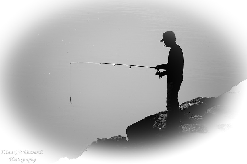 A black and white silhouette of a man fishing in the early morning light at the mouth of the Rouge River in Toronto's east end.