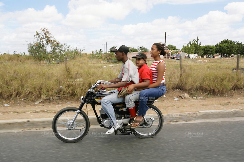 Dominican Republic. La Altagracia Province. On the road near Higüey. Three persons, a man, a boy and a woman, ride the same motorbike. © 2006 Didier Ruef