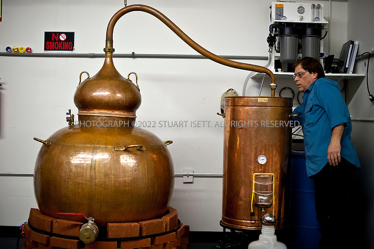 10/14/2011--Woodinville, WA, USA..Michael Sloane, distiller at Pacific distillery, checks the still...Pacific Distillery uses at Al-ambiq copper still made in Portugal. Copper has excellent heat-transfer capabilities, resistance to corrosion from wine being distilled into brandy, and copper chemically neutralizes many of the unwanted flavors that can ruin a liquor...When Pacific Distillery's Marc Bernhard started the company in 2007, he was propelled by a love of gin and a fascination with a spirit that many associated for years with art and madness: absinthe. He planned to focus on making gin and absinthe that were historically accurate from a flavor perspective..Bernhard's Voyager Dry Gin ($25.90) is similarly true to history; after 27 different experiments and tasting panels consisting of local spirit experts, he finally came to a recipe that mirrors the standard gins of 100 years ago, gins that were juniper forward, bold and memorable. ..©2011 Stuart Isett. All rights reserved.