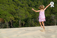 Girl (4-6) jumping in sand, arms outstretched, rear view (Licence this image exclusively with Getty: http://www.gettyimages.com/detail/200421907-001 )