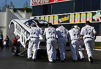 Feb 6, 2015; Pomona, CA, USA; Crew members push the car of NHRA funny car driver John Hale towards the starting line during qualifying for the Winternationals at Auto Club Raceway at Pomona. Mandatory Credit: Mark J. Rebilas-USA TODAY Sports