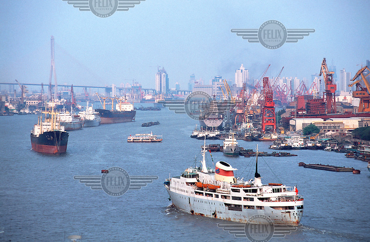 Mark Henley/Panos Pictures..China, Shanghai..Shipping in port, with Yangpu Bridge behind