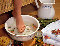 Wellness fuer die Fuesse - Frauenfuß taucht in eine Schuessel mit Kraeuterbad, Rosenblaettern und Thymian | woman's foot dipping into bowl with herbs, rose pedals and thyme