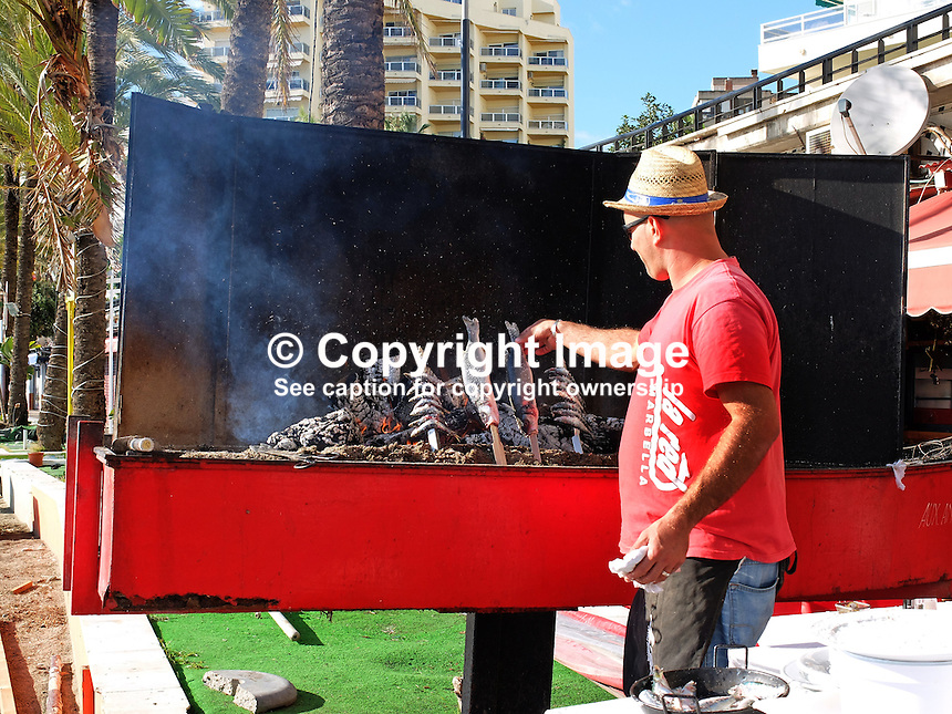 Chef at a chiringuito, open-air beach restaurant, cooking grilled sardines, seabass for clientsin Marbella, Malaga, Spain, Espana, 201412150215<br />