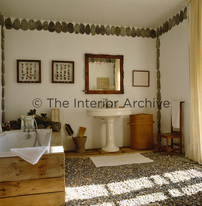 The floor of this rustic bathroom is covered in small pebbles and the walls decorated with a line of stone roof tiles