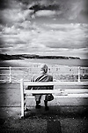 Male pensioner sitting alone on wooden bench overlooking a beach with people enjoying the sea