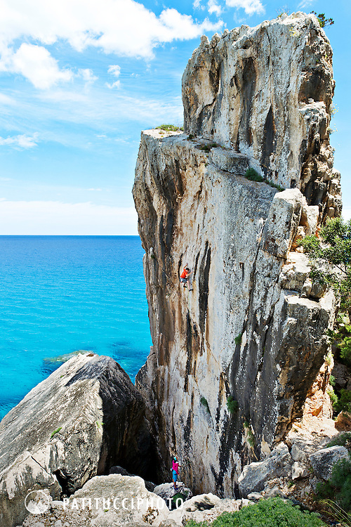 Climber on a small tower above the Mediterranean at Cala Gonone, Sardinia