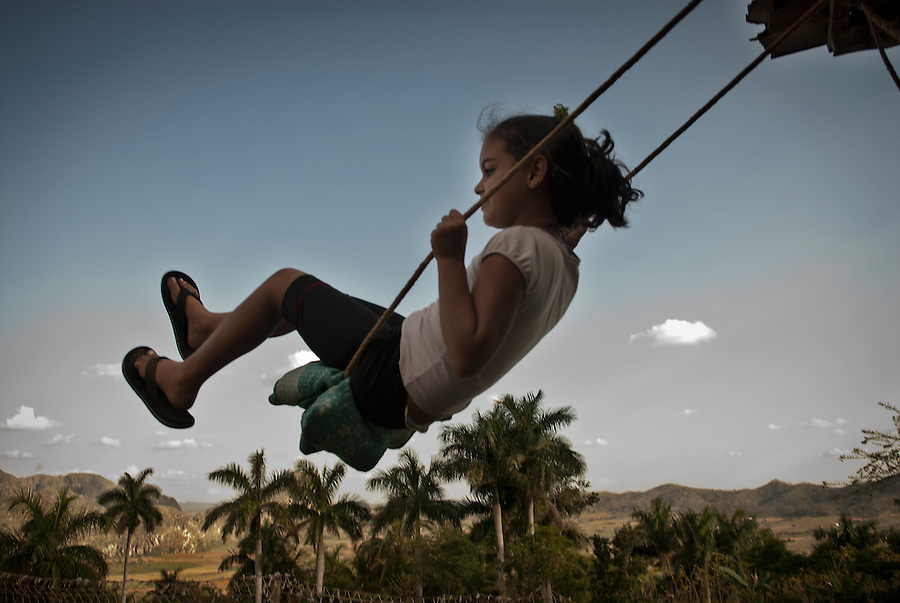 "A girl from the ""Acuaticos"" community playing in a swing in the hillside near Viñales."